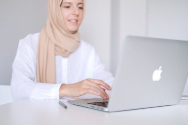 woman in white long sleeve shirt using macbook air