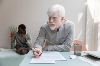 albino man writing in document